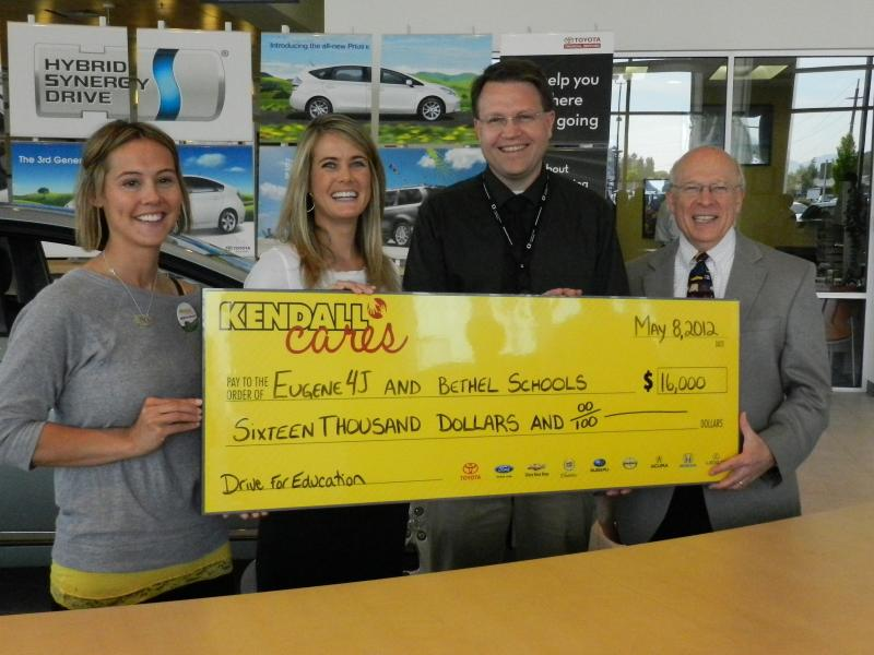 Kendall's Amy Newport and Shanley Skillern present a check to Bethel and 4J superintendents Colt Gill and Shelley Berman.