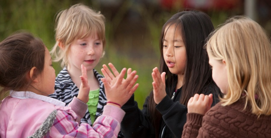 4J elementary school students play a hand-clapping game at recess